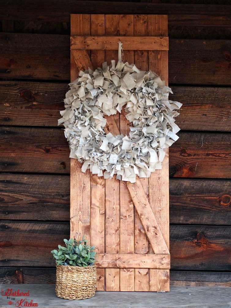 barn door with linen rag wreath leaning against a wooden plank wall