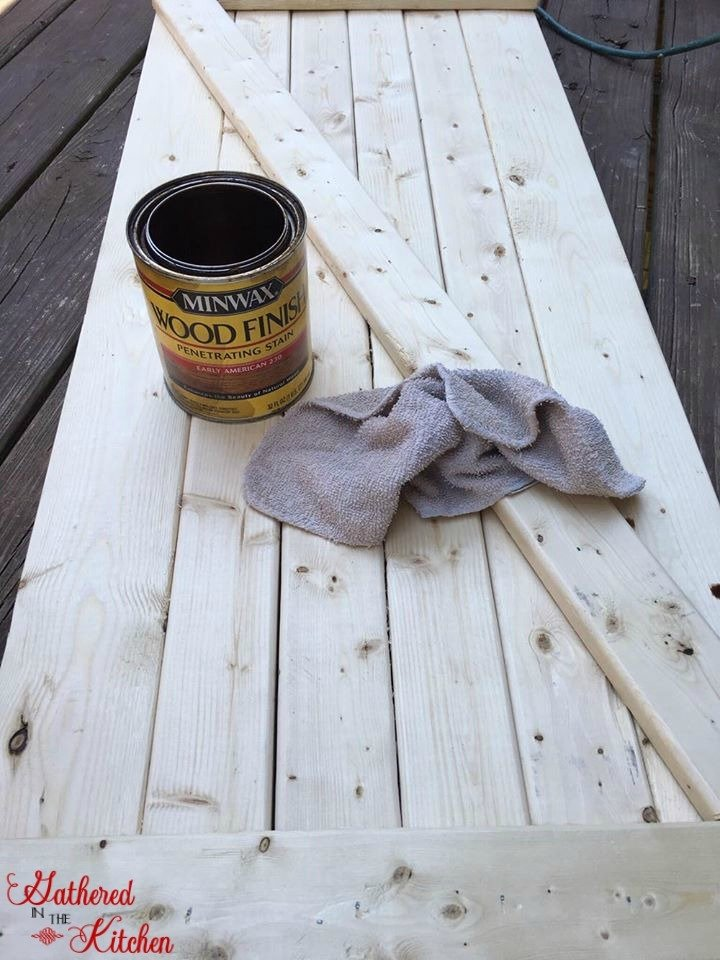 wooden barn door unfinished with a can of minwax stain and rag