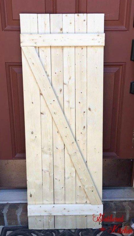 wooden barn door, unstained, leaning against a red exterior door