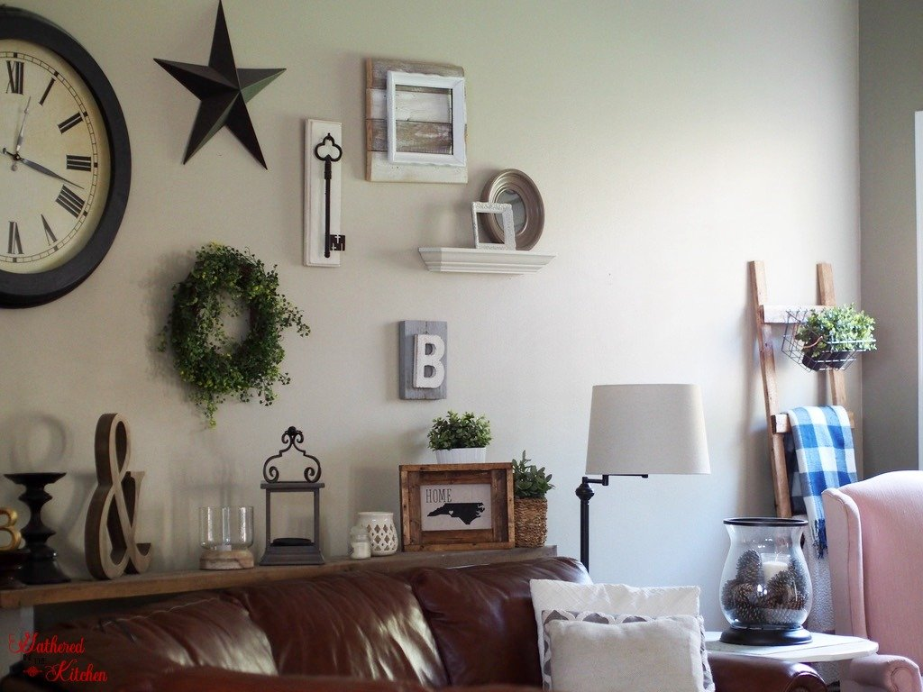 farmhouse wall gallery with clock, star, old rustic key, & sign, lamp, couch and wooden blanket ladder