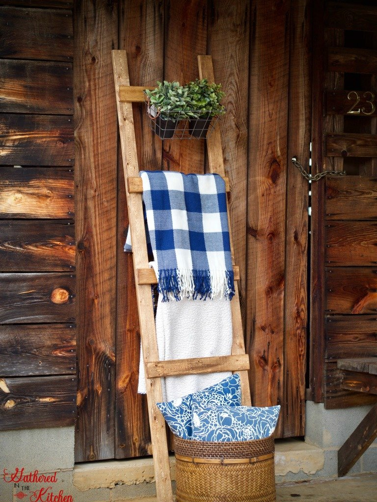 Wooden ladder blanket with green plants in a basket and a blue and white checkered blanket and white blanket leaning against a barn door with a wicker basket with blue pillows inside