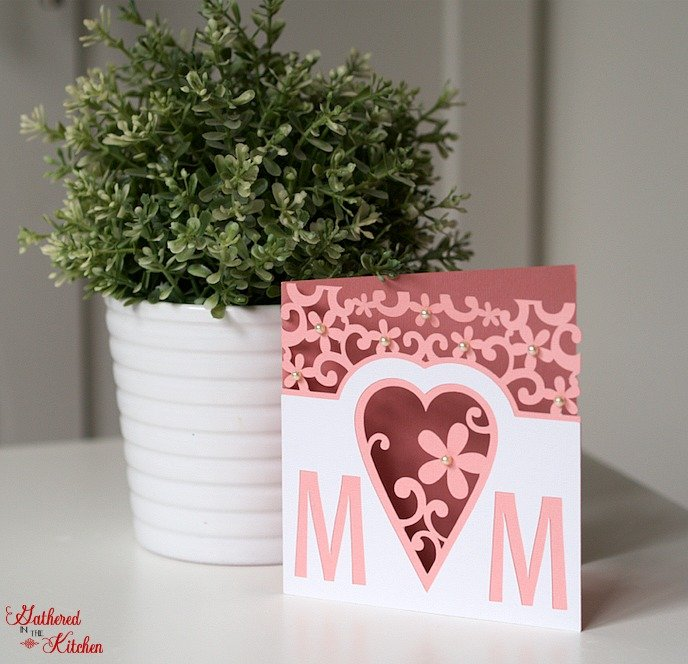 pink and white flower and heart mothers day card and a green plant in a white pot