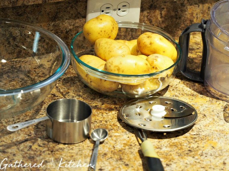 potatoes in a glass bowl with a potato slicer sitting next to it