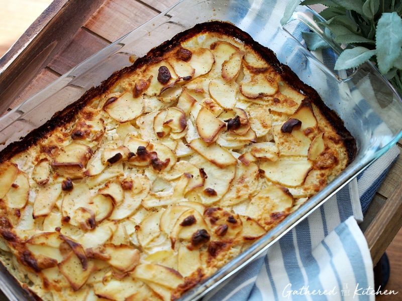 Goat cheese scalloped potatoes in a baking dish sitting on a wood tray with towel