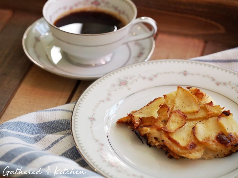 Goat cheese scalloped potatoes on a plate nexts to a cup of coffee in a teacup and saucer