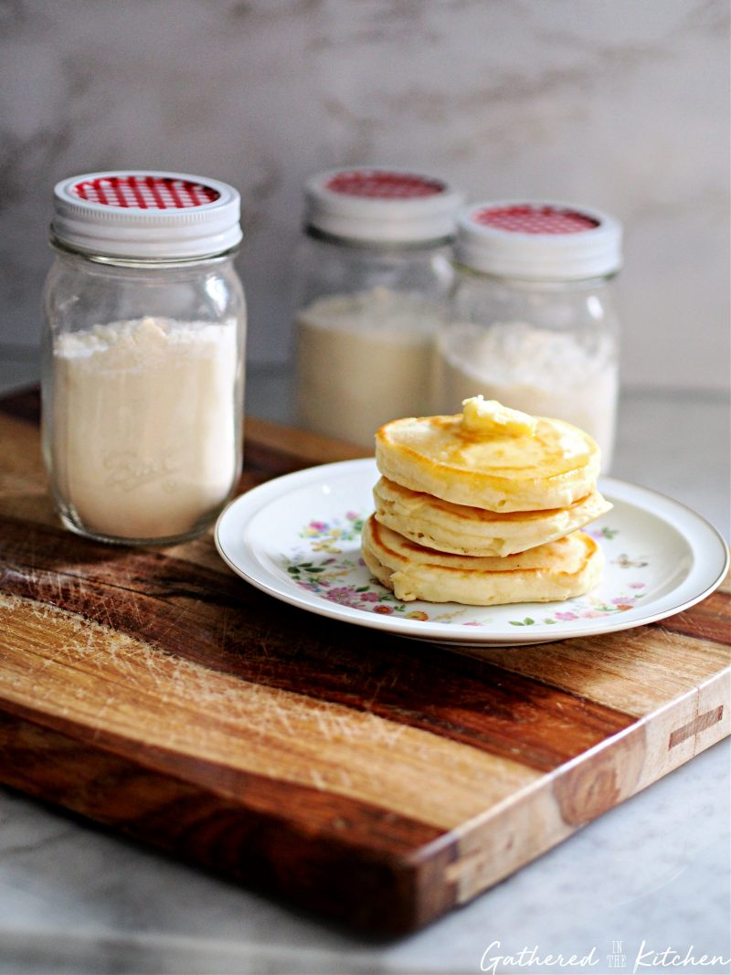 pancakes stacked on a plate with mason jars filled with dry pancake mix