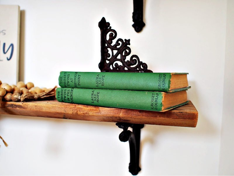 vintage green books sitting on a wooden shelf
