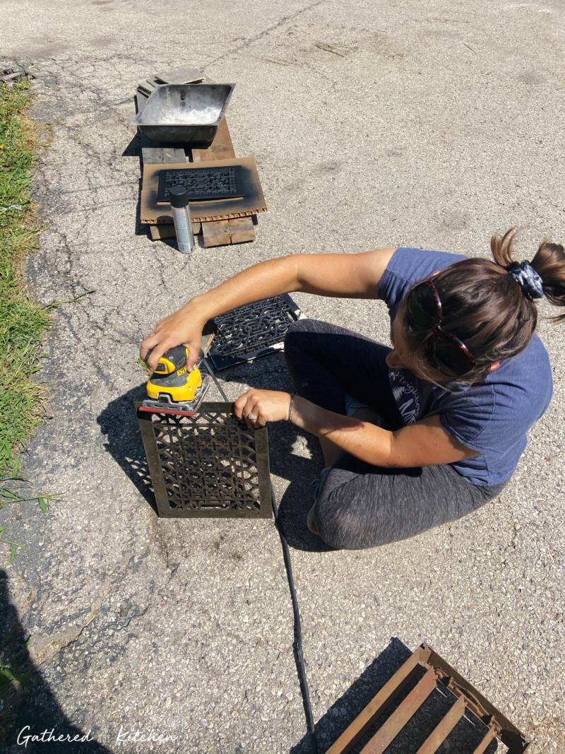woman sanding cast iron vent grate cover
