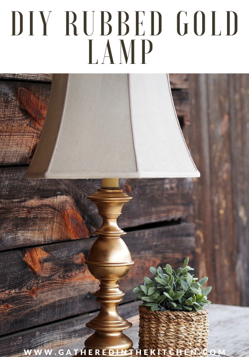rubbed gold lamp with barn wood background and green plant