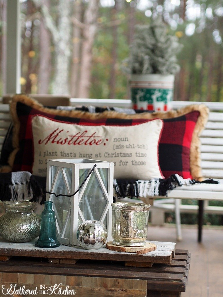 Farmhouse front porch winter decor ideas with pillows, glass candle holders and more