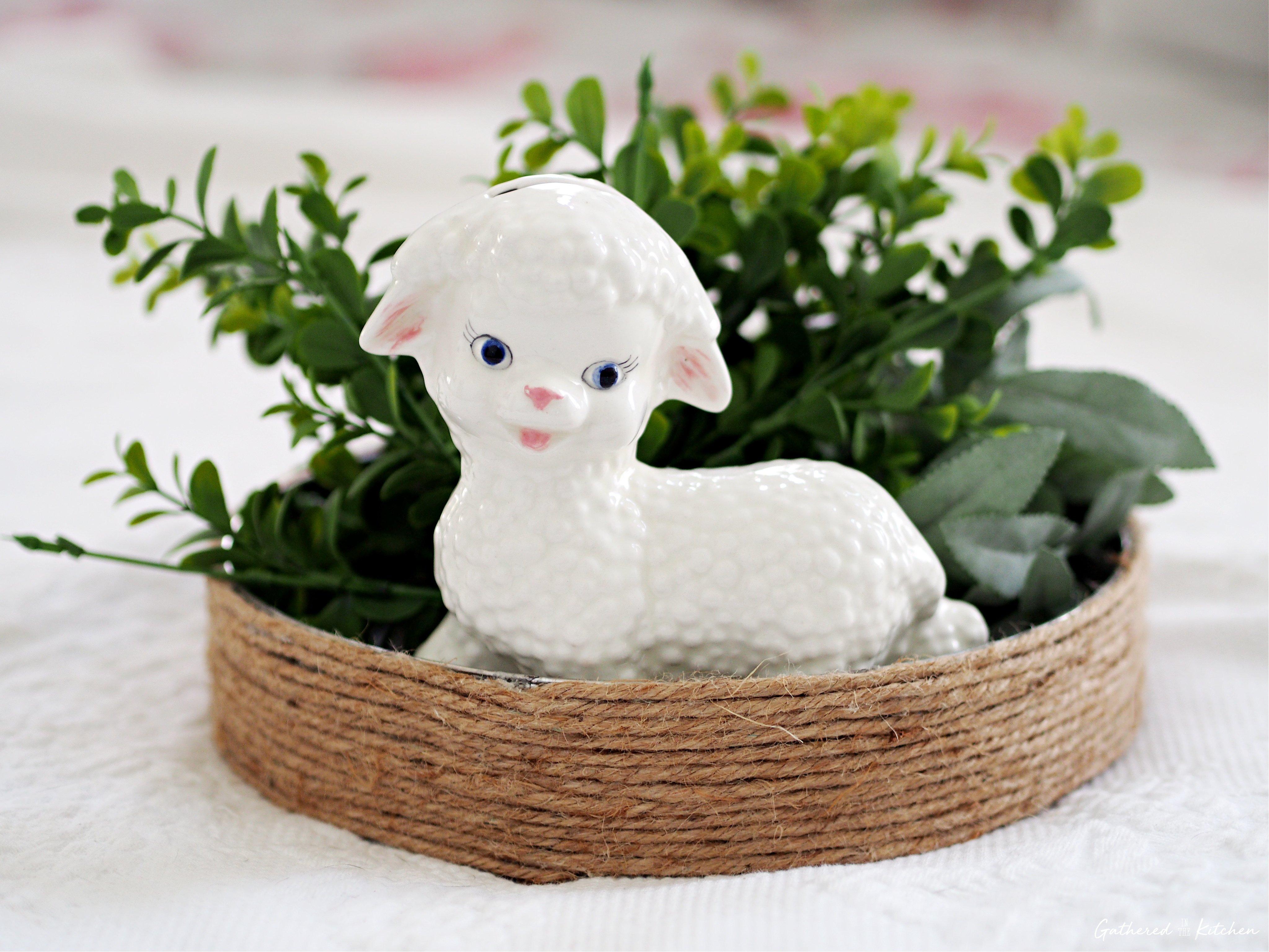 ceramic lamb with greenery behind it