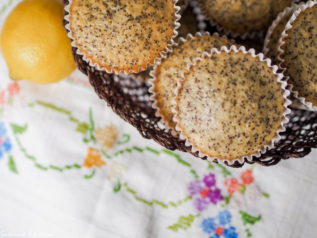 wicker basket with lemon poppy seed muffins and embroidered table cloth