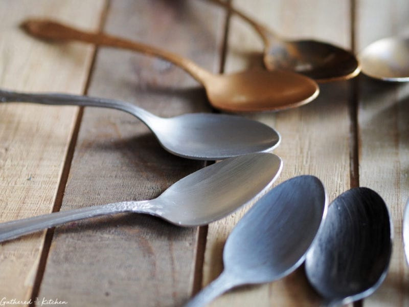 colored spoons on wooden tray