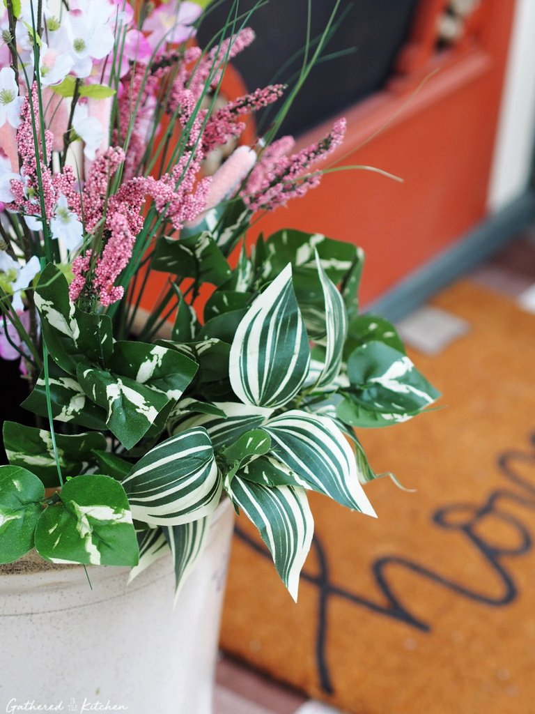 flowers and greenery in crock on front porch
