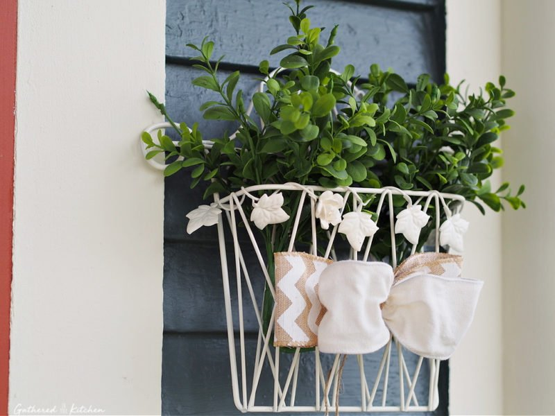 Wire basket with artificial greenery and burlap ribbon bow