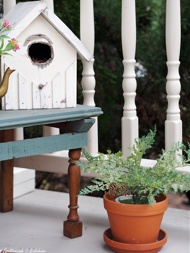 birdhouse sitting on table with greenery plant in a pot