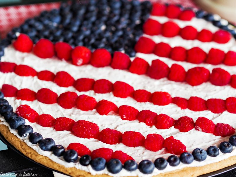 Cookie pie crust with whipped topping and blueberries and raspberries in the shape of an American Flag