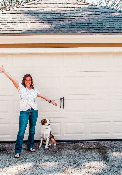 female and dog standing by garage door with carriage hardware