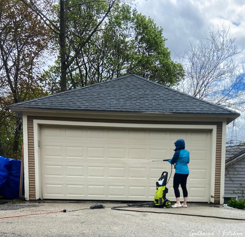 woman Pressure Washing Garage Door