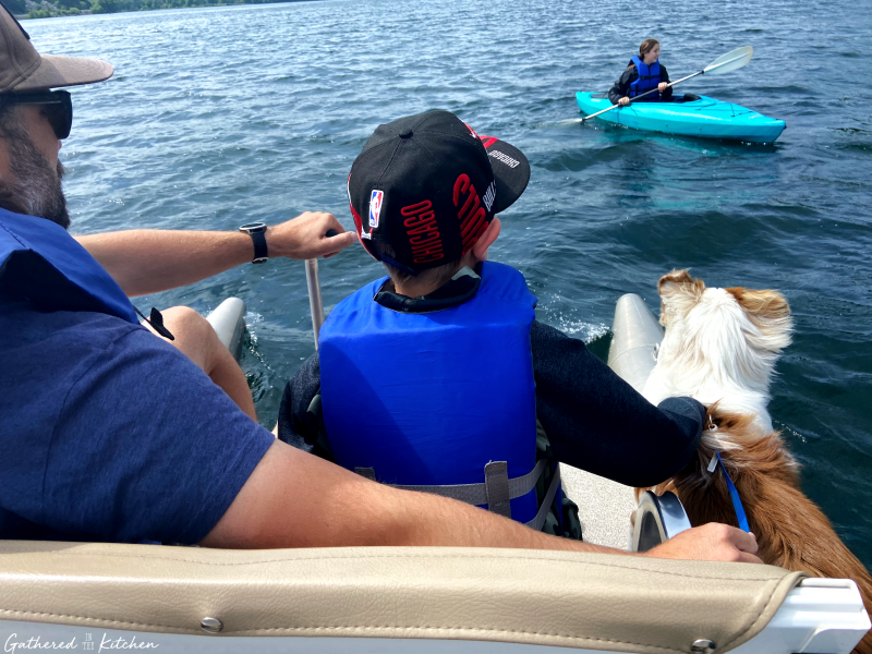 man, boy and dog on paddle boat in water and girl in kayak