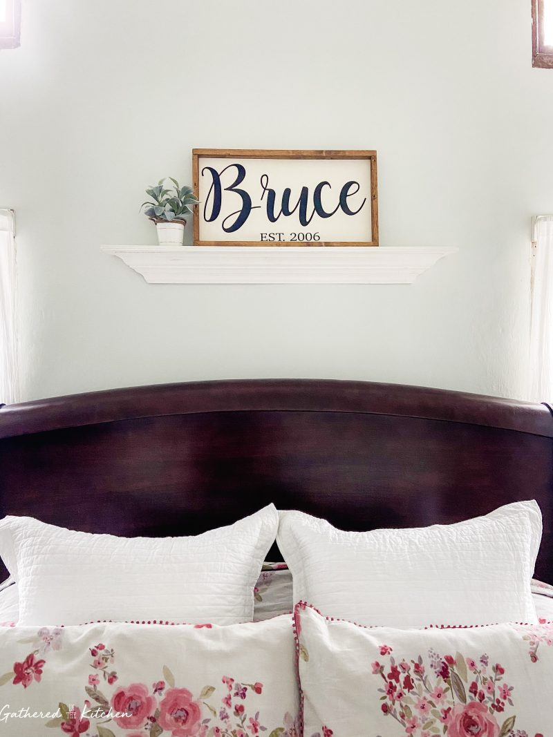 wooden shelf, wooden name and date sign and lambs ear floral arrangement above bed