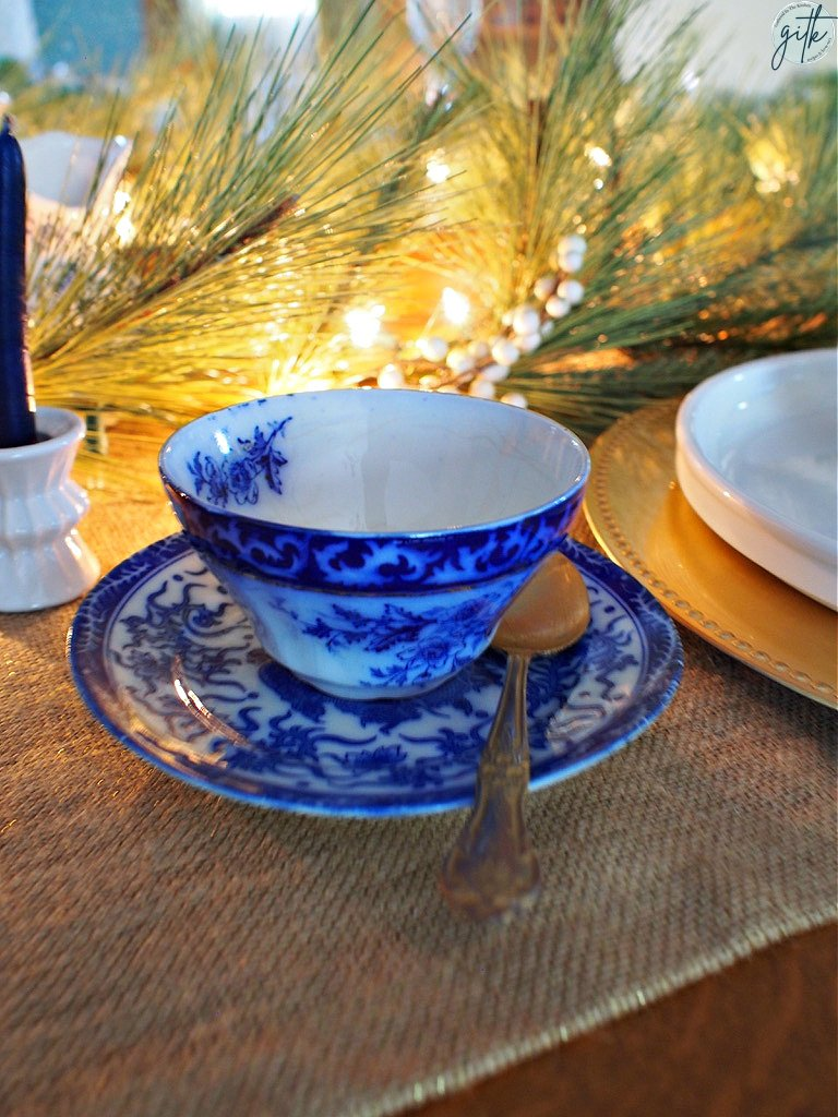 flow blue teacup and saucer on Christmas themed table