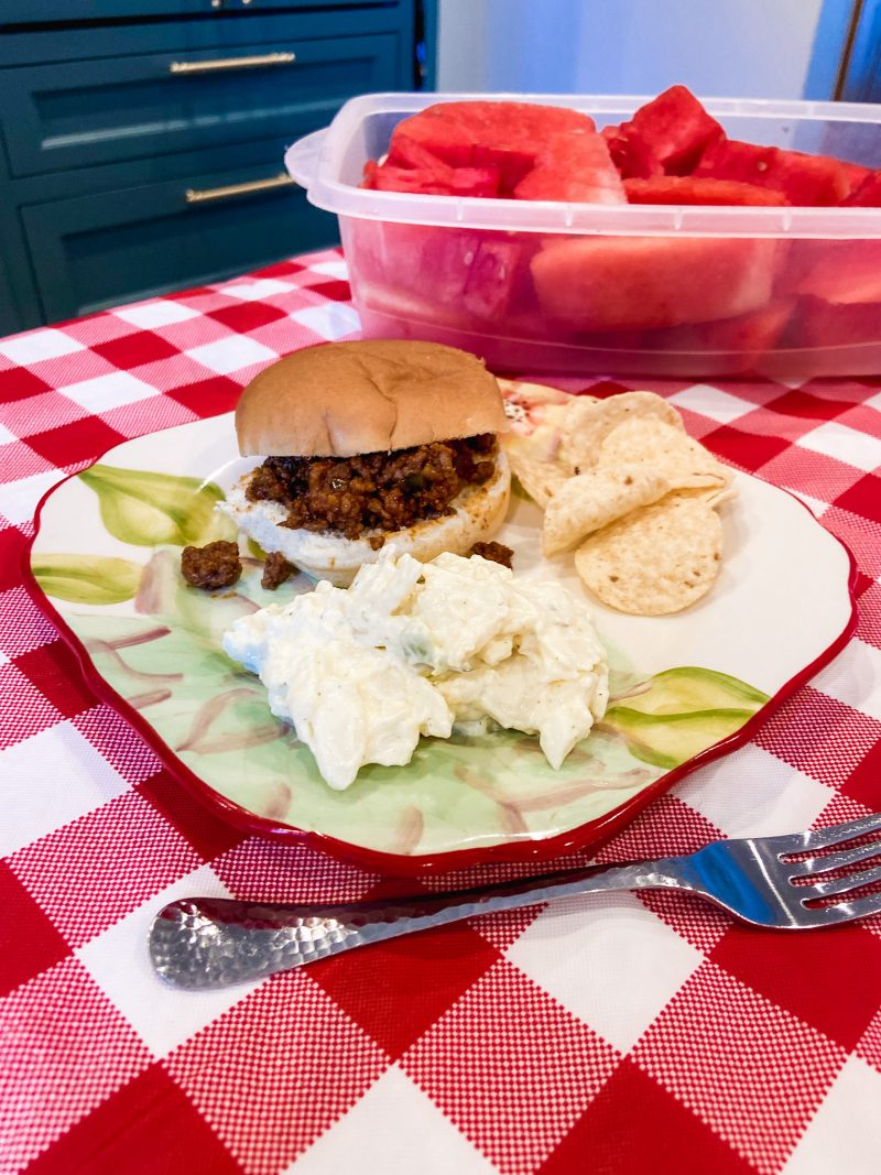 sloppy joe sandwich on a plate with potato salad and chips
