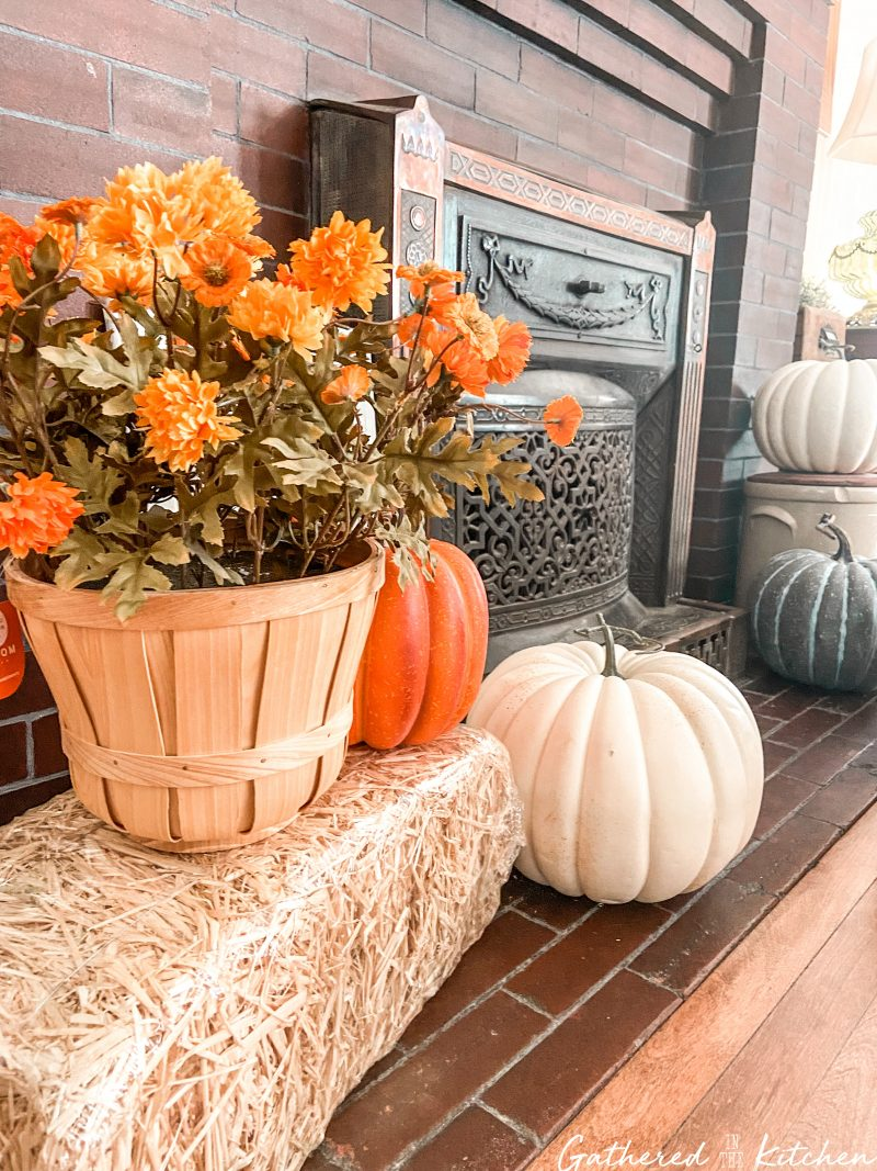 farmhouse fall decor with Hay Bale with Faux Potted Mums and Pumpkins