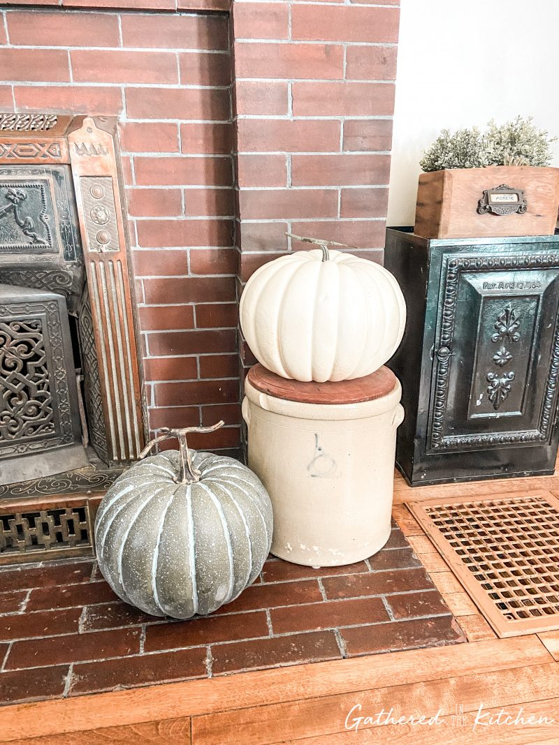 farmhouse fall decor with Large Faux Pumpkins Mixed with Antique Crocks