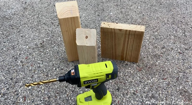 scrap pieces of wood sitting on ground with Ryboi power drill